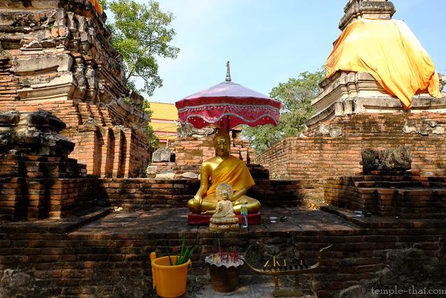 Une statue du Bouddha devant les deux stupas