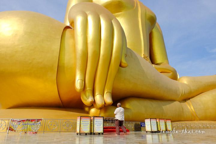 La coutume veut de toucher le majeur du bouddha