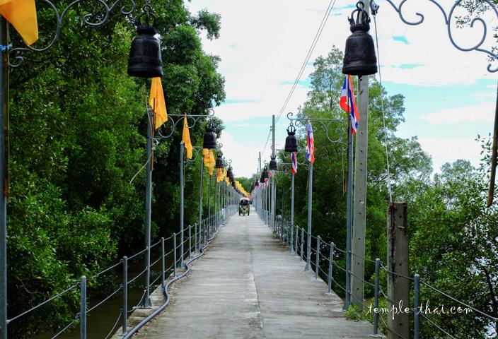 Arrivée du tuk-tuk sur la route sur pilotis, vu depuis l'entrée du temple